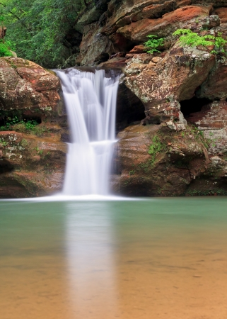 The beautiful Upper Falls, a waterfall at Old Mans Cave in Ohios Hocking Hills State Park flows with spring rains. photo
