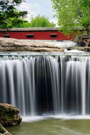cataract falls: The red Cataract Covered Bridge spans Indianas Mill Creek just upstream from beautiful Upper Cataract Falls.