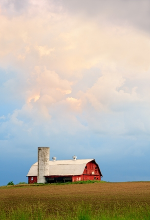 A dramatic sunset sky hangs over a red barn with silo and basketball hoop in the Midwestern United States