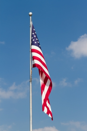 flagpoles: The flag of the United States of America flies from a flagpole in this vertical orented photograph with great detail and vibrant colors