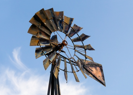 A rustic, old metal windmill stands against a blue sky with some wispy accent clouds