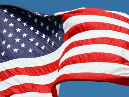 windy day: The flag of the United States of America waves in the wind against a deep blue sky