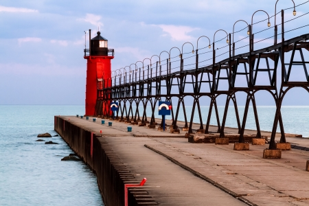 The vivid red South Haven Lighthouse, with elevated metal catwalk approach structure, is backed by a colorful morning sky over Lake Michigan  Stock Photo