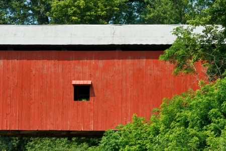 Oakalla Covered Bridge, built 1898 by J J  Daniels, carries county road 375 West over Big Walnut Creek in Putnam County, Indiana  Red covered bridge with windows is photographed close here Stock Photo - 21266852