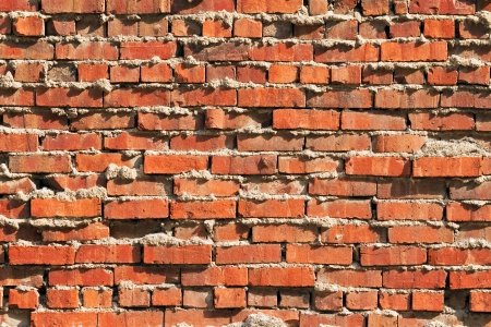 This rugged red brick wall exhibits extruded mortar and an irregular surface Stock Photo - 21896256