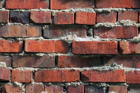 extruded: An uneven, weathered old red brick wall with extruded mortar shows texture and depth
