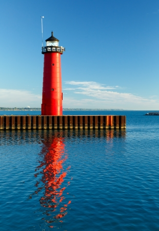 The bright red Pierhead Lighthouse at Kenosha, Wisconsin is reflected in early morning light on the waters of Lake Michigan