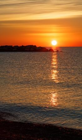 The sun rises brilliantly over a rocky breakwater on Lake Michigan in Kenosha, Wisconsin  Stock Photo