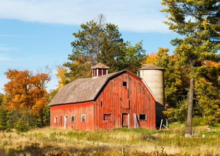An old red barn with silo is surrounded by trees with colorful fall foliage  Shot in rural Wisconsin