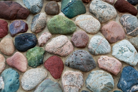 This photographic still features a masonry stone wall with rocks in a very wide range of colors and textures