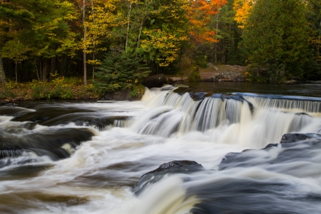 Whitewater flows over dark rock ledges with colorful fall foliage all around at Bond Falls in Michigan photo