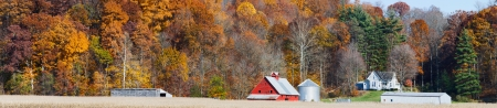 An Indiana farm with red barn is backed by a hillside full of colorful fall foliage in this panoramic photograph  写真素材