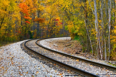 railway transportation: Railroad track curve around the bend and out of sight through trees with beautiful fall foliage  Shot in rural central Indiana