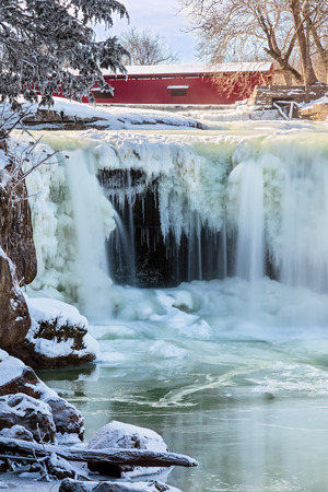 cataract falls: Indiana s Upper Cataract Falls is frozen with a red covered bridge spanning the creek upstream  Lieber State Recreation area near Cloverdale, Indiana