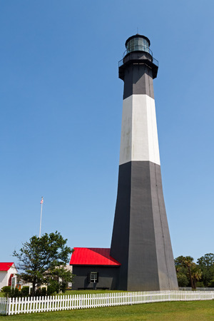 tybee island: The black and white Tybee Island Lighthouse, near Savannah, Georgia, stands tall against a clear blue summer sky