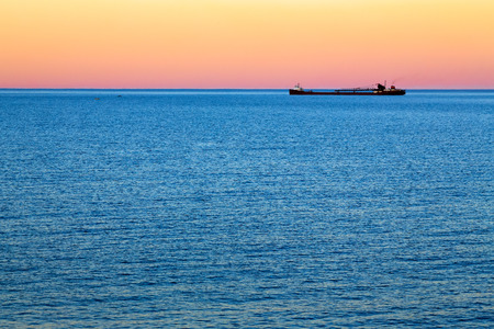 A huge freighter ship traverses the horizon at sundown on Lake Superior  photo