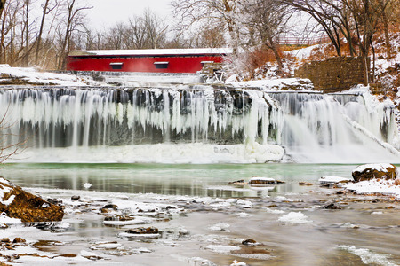 cataract falls: Whitewater flows over icicles at a frozen Upper Cataract Falls with a red covered bridge upstream  Photographed on Mill Creek near Cloverdale, Indiana