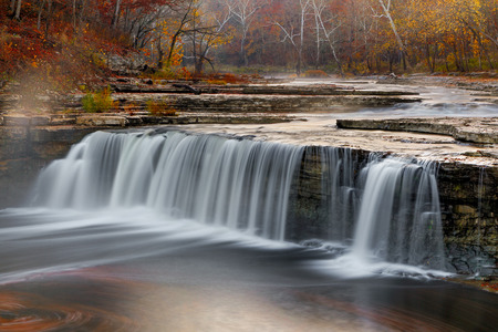 Morning mist rises over Indiana s Lower Cataract Falls surrounded by a vibrant autumn landscape  photo