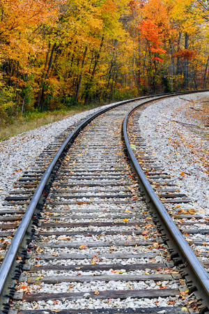Railroad tracks curve through a landscape full of colorful fall foliage  photo