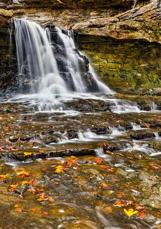 countryside landscape: Water cascades over the Canyon Falls and past colorful autumn leaves in Indiana