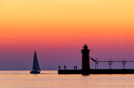 A vividly colorful twilight sky silhouettes a sailboat, people, and the lighthouse at South Haven, Michigan on Lake Michigan