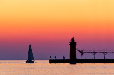 lake michigan lighthouse: Un cielo v�vidamente colorido crep�sculo siluetas de un velero, la gente, y el faro de South Haven, Michigan, el lago Michigan