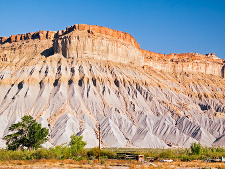 Sandstone mesas with shale bases are found in the Utah badlands east of Capitol Reef National Park  photo