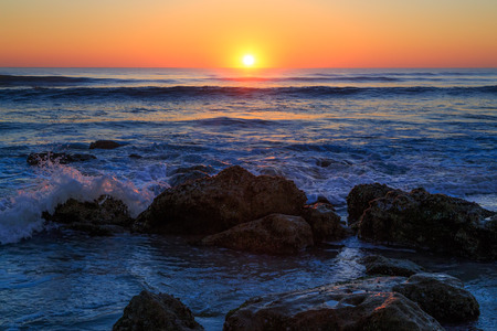 coquina: The sun rises over the Atlantic Ocean with waves breaking on a Florida beach covered with coquina stone