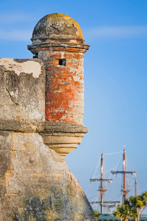 coquina: A round corner sentry box, on an old St  Augustine, Florida Spanish fort called the Castillo de San Marcos, is backed by the tall masts of a Spanish Galleon in Matanzas Bay