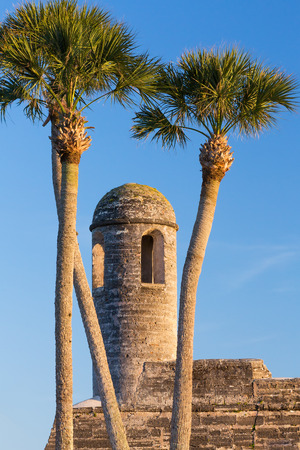 The bell tower on the San Carlos Bastion corner of the Castillo de San Marcos, a seventeenth century Spanish fortress in St  Augustine, Florida, is framed by tall palm trees  photo
