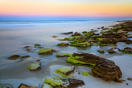 coquina: The setting sun paints the opposite horizon over the Atlantic Ocean with color along a Florida beach with an outcropping of natural coqunia stone  Waves have a smooth, dreamy appearance from a long exposure