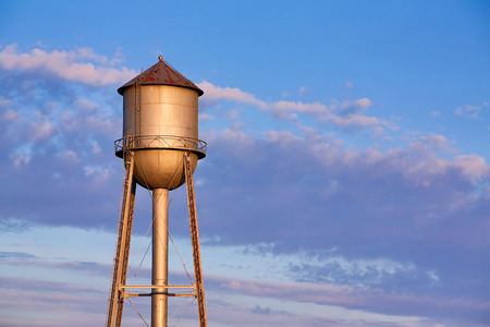 water tank: An old metal water tank, in the light of the morning sun, stands tall against a colorful cloudy sky in America Stock Photo