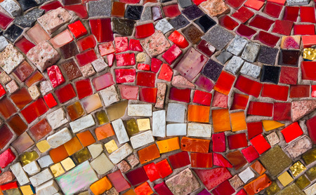 Colorful pieces of glass and stone pressed into masonry make a decorative and colorful mosaic design  photo