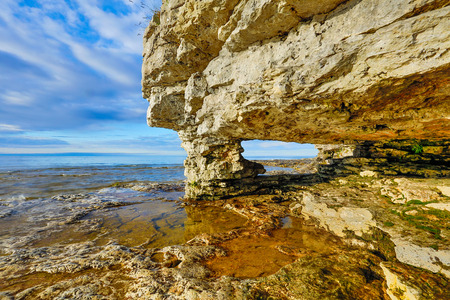 stoney point: A rock arch window has been eroded by the waves at Door County, Wisconsin