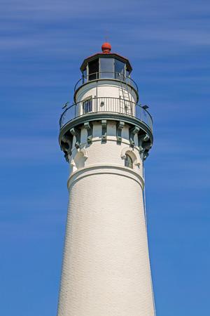 lake michigan lighthouse: La parte superior del faro del punto del viento, en la orilla del lago Michigan de Racine, Wisconsin, se yergue contra un claro cielo azul con tenues nubes blancas Foto de archivo