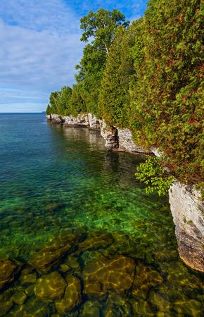 미시간 호수의 맑은 물 도어 카운티, 위스콘신에있는 동굴 포인트의 견고한 바위 해안선을 충족
