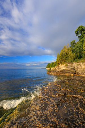 stoney point: Gentle waves splash on the rocky shoreline of Door County, Wisconsin Stock Photo