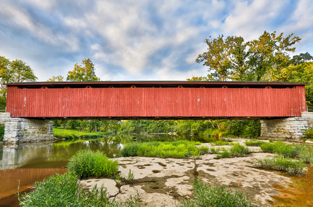cataract falls: The Cataract Falls Covered Bridge Crosses Indianas Mill Creek with a cloudy blue sky above