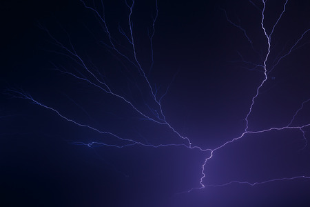 Lightning arcs in the night sky in dramatic fashion  Stock Photo