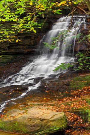 hemlock: Honey Run Falls cae por un acantilado de arenisca enmarcado por el colorido follaje de otoño en el condado de Knox rural, Ohio.