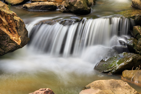 Water flowing over and around stone boulders in a West Virginia creek is photographed with a long exposure. photo