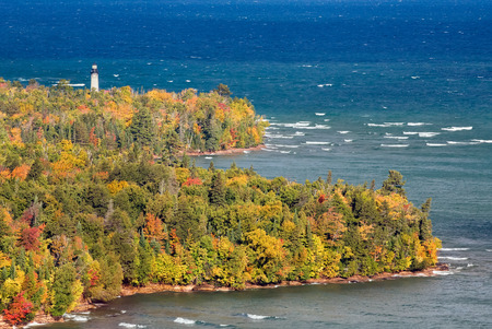 upper peninsula: The Au Sable Light Station, surrounded by colorful fall foliage, stands on the Lake Superior shore of Michigans Upper Peninsula at Pictured Rocks National Lakeshore near Grand Marais.