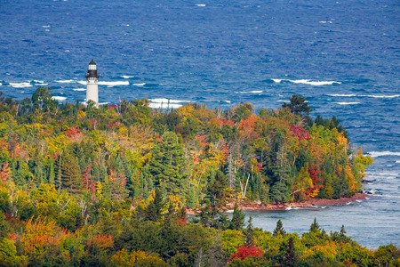 autumn colors: Au Sable Light Station, a lighthouse on the Lake Superior Coast of Michigans Upper Peninsula, is surrounded by colorful autumn foliage.