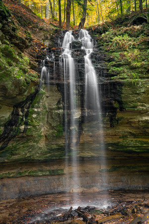 rudy: Tannery Falls, a secluded waterfall in Munising, Michigan plunges into a canyon below with fall foliage above.