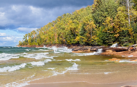 elliot: Elliot Falls (Miners Beach Falls) cascades into Lake Superior as waves break on the autumn coast of Pictured Rocks National Lakeshore in Michigan\