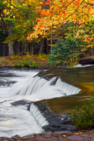 watersmeet: Colorful autumn foliage surrounds a cascade at Bond Falls, a very beautiful multistage waterfall in Michigans Upper Peninsula Stock Photo