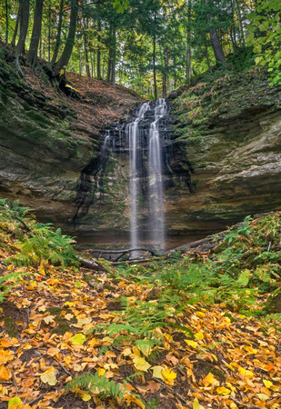 upper peninsula: Tannery Falls, a waterfall near the Upper Peninsula Michigan town of Munising, pours over a rocky cliff in the autumn forest.