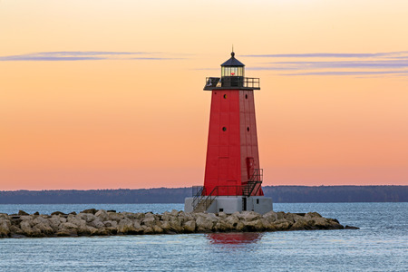lake michigan lighthouse: El cielo se ilumina con color que el sol se levanta en el faro rojo en Manistique en la costa del Lago Michigan de Michigan