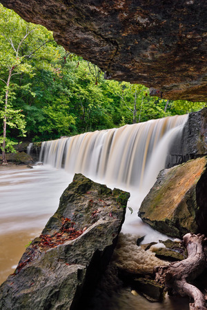 Anderson Falls, a wide, beautiful waterfall near Columbus, Indiana, has a rock grotto on one side with fallen boulders. Stock Photo