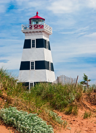 navigation aid: The distintive black and white striped wooden West Point Lighthouse, with red top and green Fresnel lens, is the tallest on Canada Stock Photo